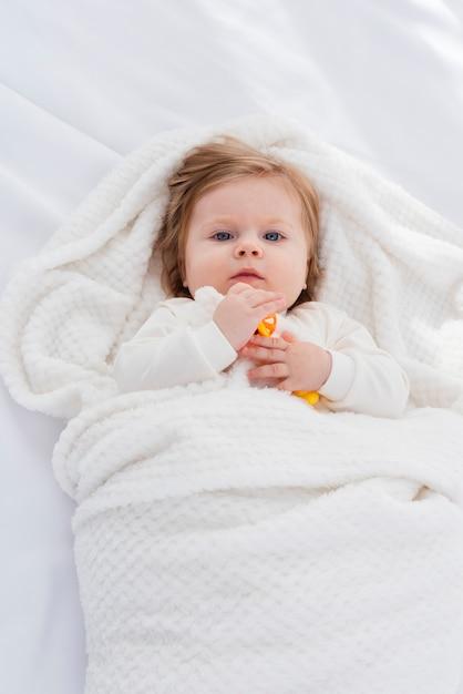 Postura plana de bebê no cobertor branco Foto gratuita