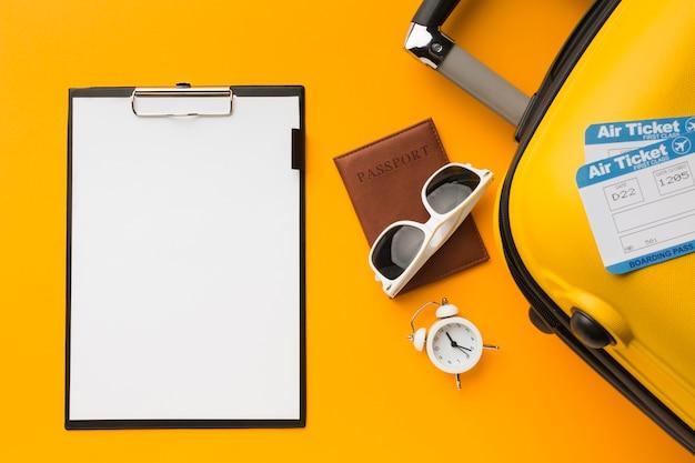Postura plana de bloco de notas com bagagem e itens essenciais de viagem Foto gratuita