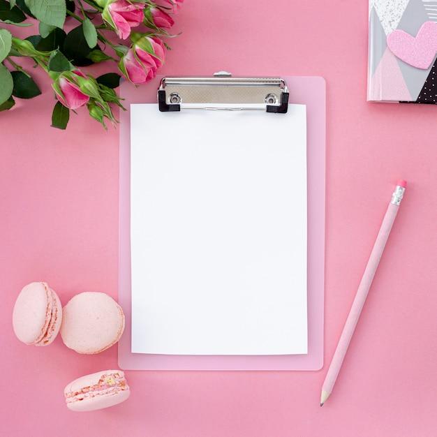 Postura plana de bloco de notas com caneta e macarons Foto gratuita