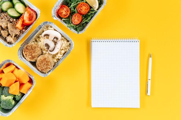 Postura plana de caderno com caneta e refeições em caçarolas Foto gratuita