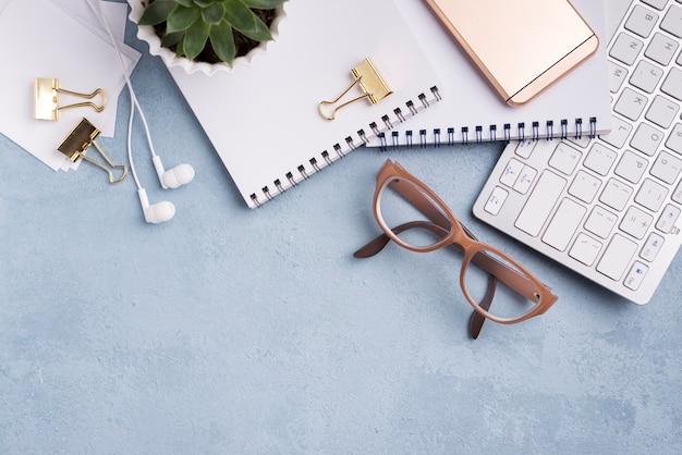 Postura plana de cadernos com teclado e planta suculenta Foto gratuita