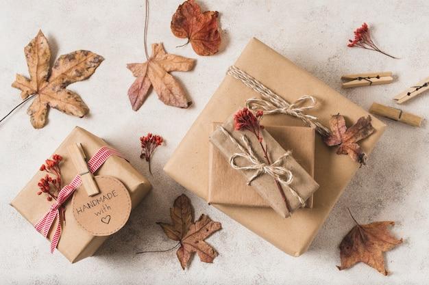 Postura plana de caixas de presente com folhas mortas e pregadores de roupas Foto gratuita