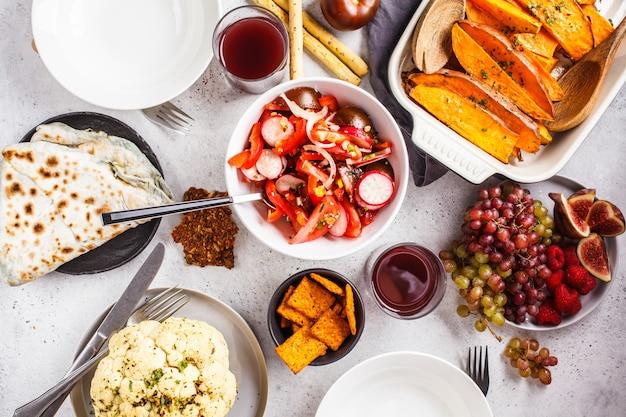 Postura plana de comida vegetariana: batata-doce assada, couve-flor, frutas, salada de legumes e tortilla com verduras no fundo branco. Foto Premium