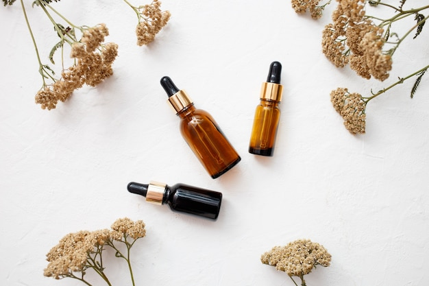 Postura plana de conta-gotas de vidro de frasco de produtos de óleo essencial para a pele para mock up em estilo minimalista com fundo branco. Foto Premium