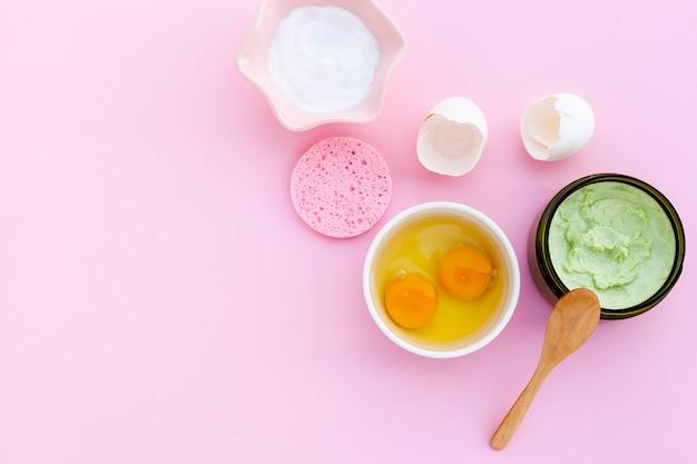 Postura plana de creme e ovos no bacground rosa com espaço de cópia Foto gratuita