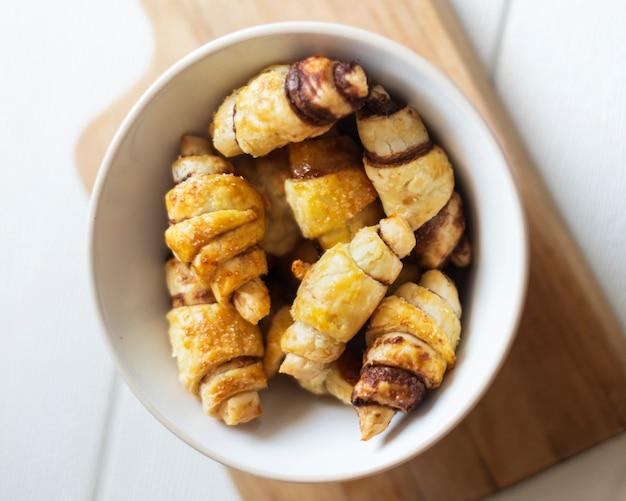 Postura plana de croissants de chocolate na tigela Foto gratuita