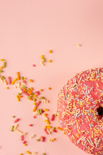 Postura plana de donut com vidro e granulado colorido Foto gratuita