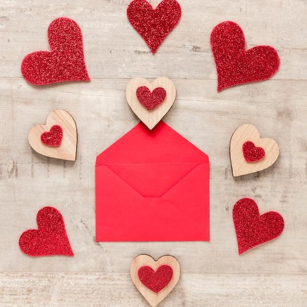 Postura plana de envelope com corações em fundo de madeira Foto gratuita