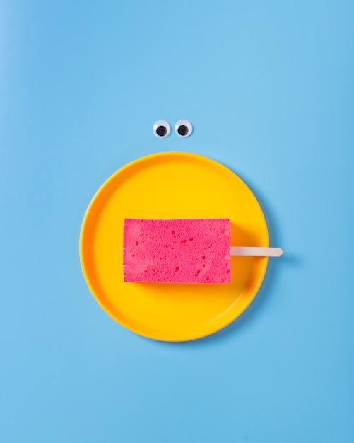 Postura plana de esponja no prato sobre fundo azul Foto gratuita