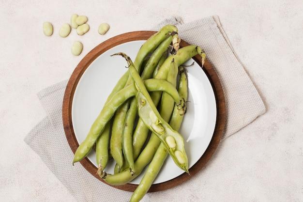Postura plana de feijão e alho no prato Foto gratuita