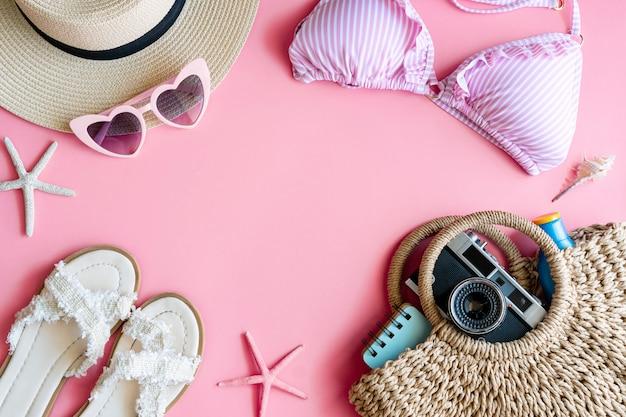 Postura plana de itens de verão com biquíni rosa pastel, chapéu de praia, chinelo, bolsa, câmera, protetor solar, notebook e óculos de sol, vista superior e espaço de cópia. conceito de verão. Foto Premium