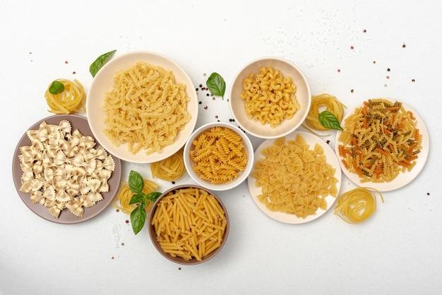 Postura plana de macarrão em tigelas no fundo liso Foto gratuita