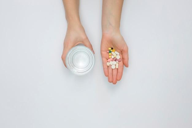Postura plana de mão segurando comprimidos e copo de água Foto gratuita
