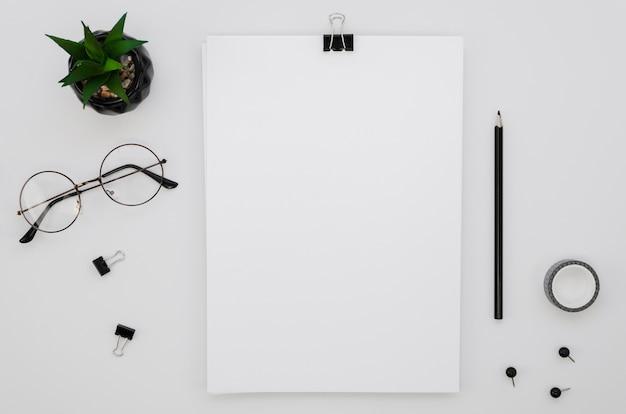 Postura plana de material de escritório com óculos e planta Foto Premium