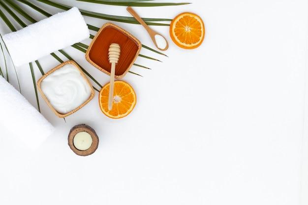 Postura plana de mel de manteiga corporal e laranja em fundo branco Foto gratuita