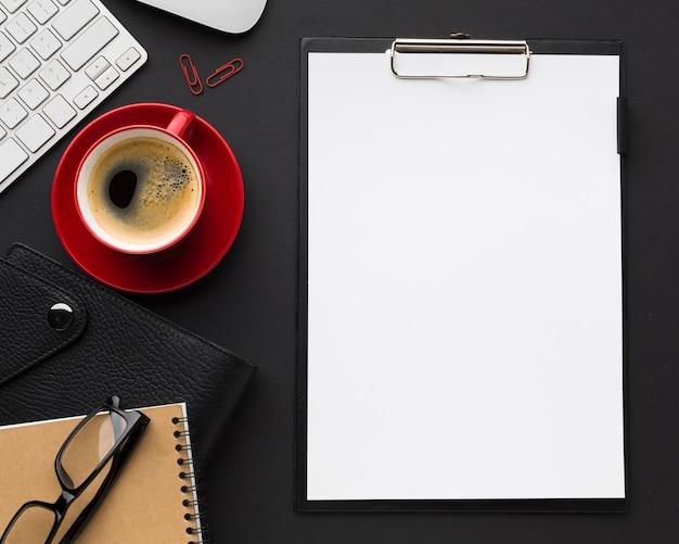 Postura plana de mesa com copo de papel e café Foto gratuita
