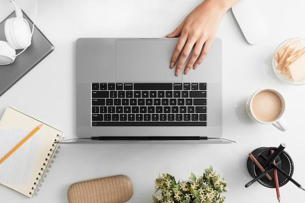 Postura plana de mesa com mão e computador portátil Foto gratuita