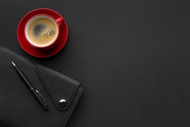 Postura plana de mesa de trabalho com agenda e xícara de café Foto gratuita