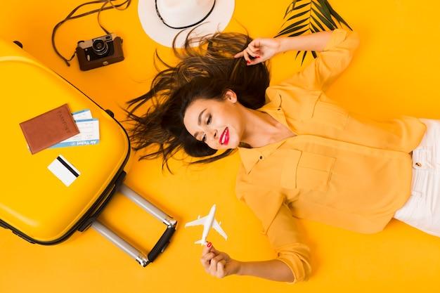 Postura plana de mulher posando ao lado de fundamentos de viagem Foto gratuita