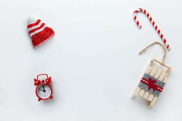 Postura plana de natal, chapéu de inverno gorro, pirulito, pequeno relógio analógico vermelho, trenó no fundo branco Foto Premium