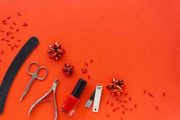 Postura plana de natal de acessórios de manicure e esmaltes com decorações do feriado em um fundo vermelho. espaço para texto. Foto Premium