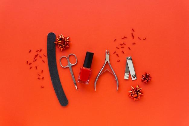 Postura plana de natal de acessórios de manicure e esmaltes com decorações do feriado em um fundo vermelho. Foto Premium