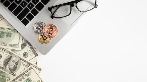 Postura plana de notas de dólar perto de laptop Foto gratuita