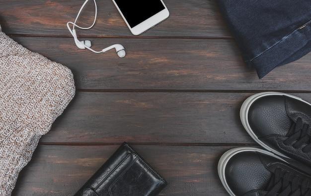 Postura plana de outono ou inverno pano e acessório na mesa de madeira com espaço de cópia. suéter de lã, telefone com fones de ouvido, jeans azul, tênis de couro e bolsa Foto Premium