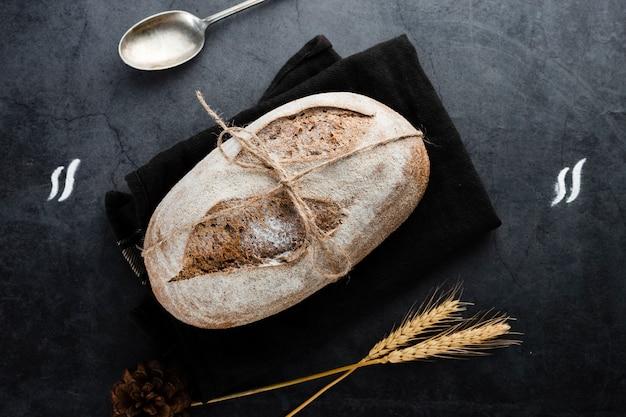 Postura plana de pão e trigo em fundo preto Foto gratuita