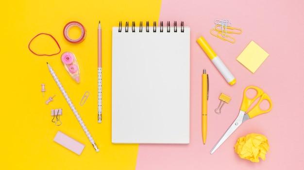 Postura plana de papelaria de escritório com notebook e elásticos Foto gratuita