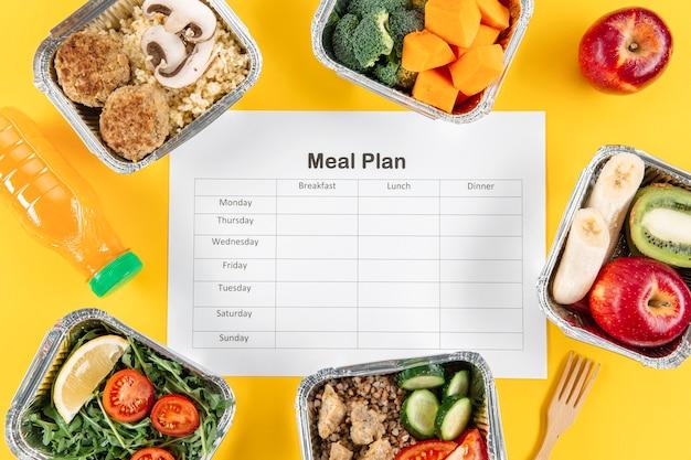Postura plana de plano de refeições com caçarolas com frutas e legumes Foto Premium