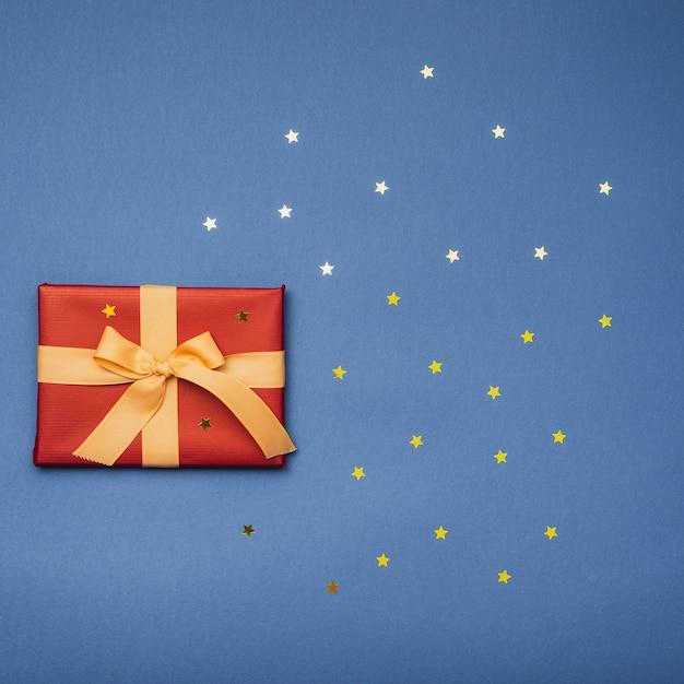 Postura plana de presente de natal com estrelas douradas Foto gratuita