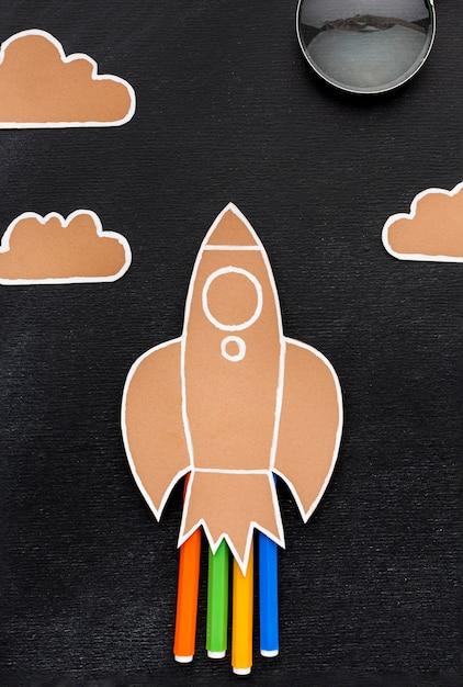 Postura plana de volta ao foguete escolar com lápis e nuvens Foto gratuita