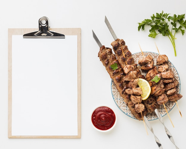 Postura plana do bloco de notas com prato de kebab e ketchup delicioso Foto gratuita