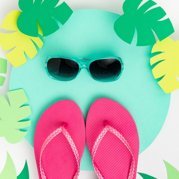 Postura plana do conceito de verão com chinelos Foto gratuita