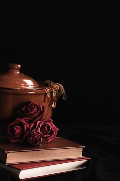 Pote com rosas e geléia em fundo preto Foto gratuita