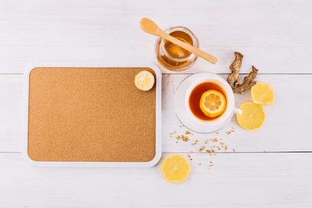 Pote de chá de mel e limão perto de gengibre no fundo de madeira Foto gratuita