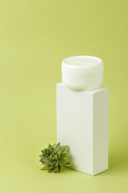 Pote de creme cosmético branco em suporte Foto Premium