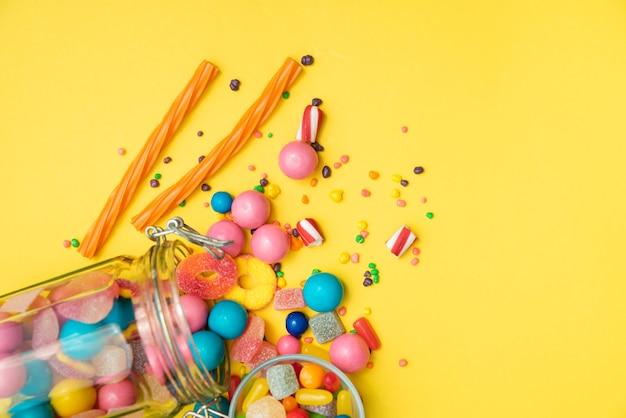 Pote de doces virado sobre a mesa Foto gratuita