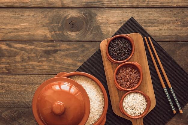 Pote de grãos de arroz cru com tampa e tigela de arroz na placemat com pauzinhos Foto gratuita