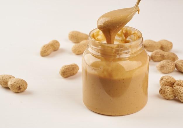 Pote de manteiga de amendoim e amendoim com casca em uma mesa branca, vista lateral, nozes moídas frescas Foto Premium