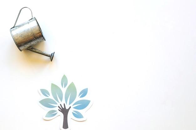 Pote de rega sobre a árvore de papel Foto gratuita