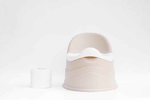 Pote infantil bege com bacia removível fica e ao lado de um rolo de papel higiênico Foto Premium