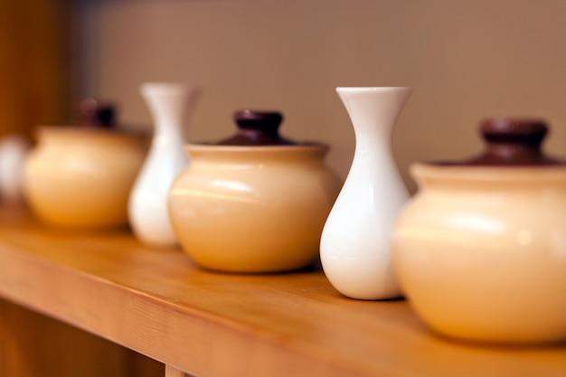 Potes de cerâmica bege e pequenos vasos brancos Foto Premium