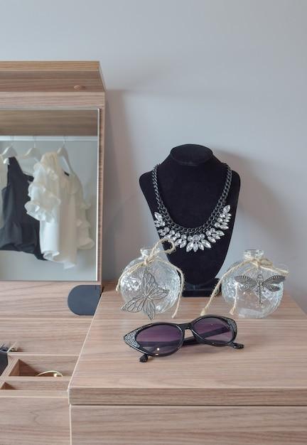 Potes de cristal e colar na penteadeira de madeira Foto Premium
