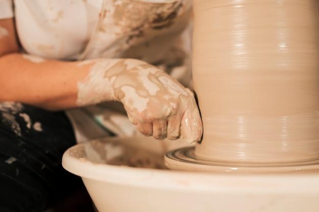 Potter feminino profissional suavização de argila na roda de oleiro Foto gratuita