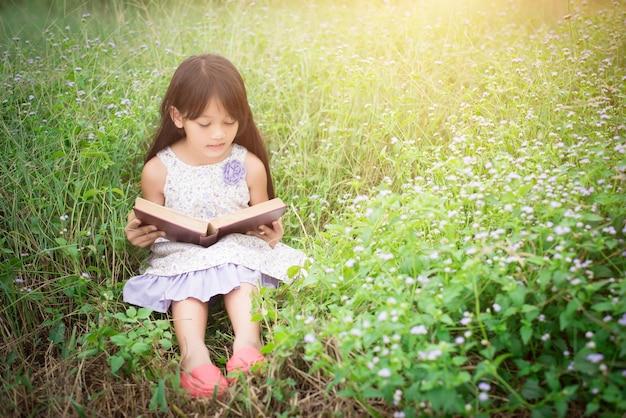 Pouco livro de leitura em natureza menina asiática bonito. Foto gratuita