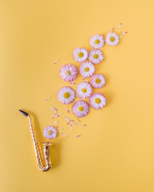 Pouco saxofone dourado e margaridas cor de rosa em fundo laranja. conceito de cartão postal Foto Premium