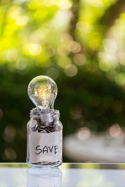 Poupança de depósito de moedas em um frasco de vidro transparente Foto Premium