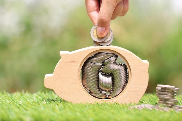 Poupar dinheiro para preparar no futuro conceito, mão de mulher colocando uma moeda em madeira de cofrinho Foto Premium